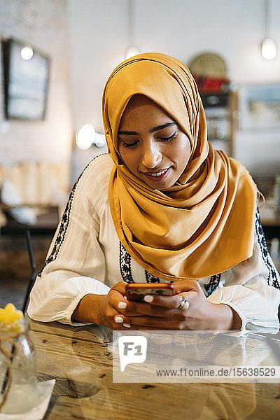 Junge muslimische Frau  die in einem Café einen gelben Hijab trägt und ein Smartphone benutzt
