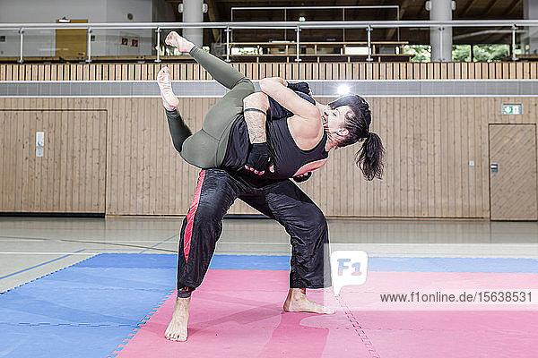 Kickboxerin übt mit Trainerin in Sporthalle