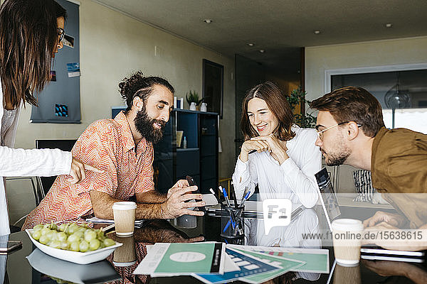 Friends working together on table at home sharing smartphone