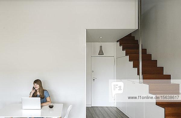 Porträt einer lächelnden Frau am Telefon  die am Tisch mit Laptop und Tasse Kaffee sitzt