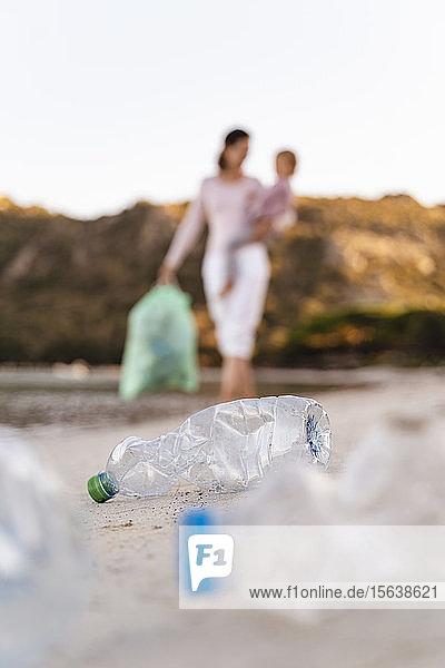 Frau mit Kindern am Arm sammelt leere Plastikflaschen am Strand