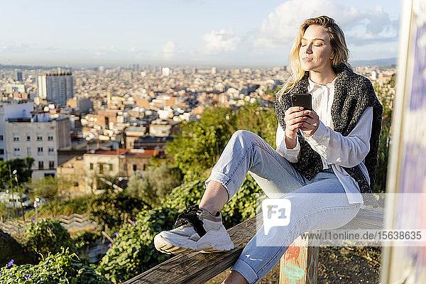 Junge Frau sitzt auf einem Geländer über der Stadt und hält ein Handy in der Hand  Barcelona  Spanien