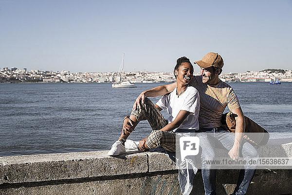 Glückliches junges Paar sitzt auf einer Mauer am Wasser  Lissabon  Portugal
