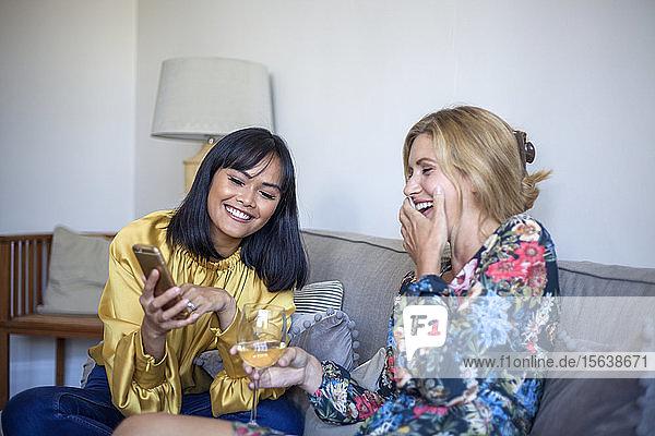 Zwei Freunde sitzen auf der Couch  unterhalten sich  schauen auf das Smartphone