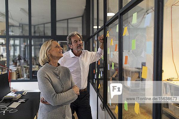 Kollegen schauen auf Haftnotizen an einer Glasscheibe im Büro