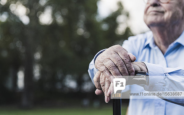 Hands of senior man leaning on walking stick  close-up