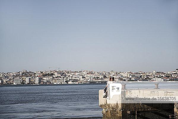 Junges Paar sitzt am Pier am Wasser  Lissabon  Portugal