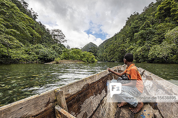 Papuan boy on a boat on the Warsambin River; West Papua  Indonesia