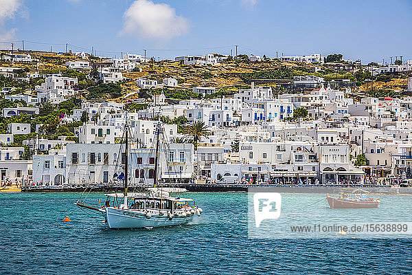 Coast of Greek island on the Mediterranean with boats near the waterfront and white buildings along the shore; Mykonos Town,  Mykonos Island,  Cyclades,  Greece