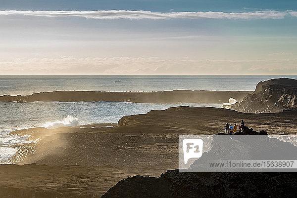 Friends enjoying the view near Reykjanes Lighthouse at sunset  Reykjanes Peninsula; Iceland