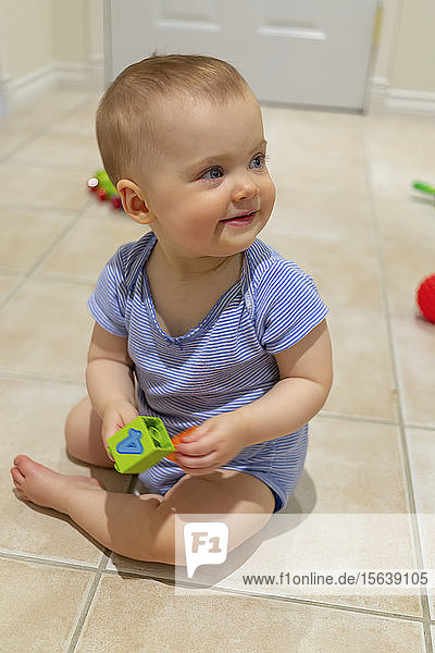 A baby girl sits on the floor at home playing with a toy; Vancouver  British Columbia  Canada