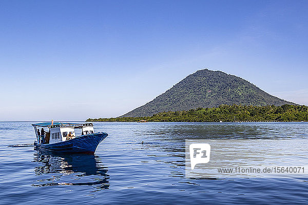 Diving boat with Manado Tua in the background  Bunaken National Marine Park; North Sulawesi  Indonesia