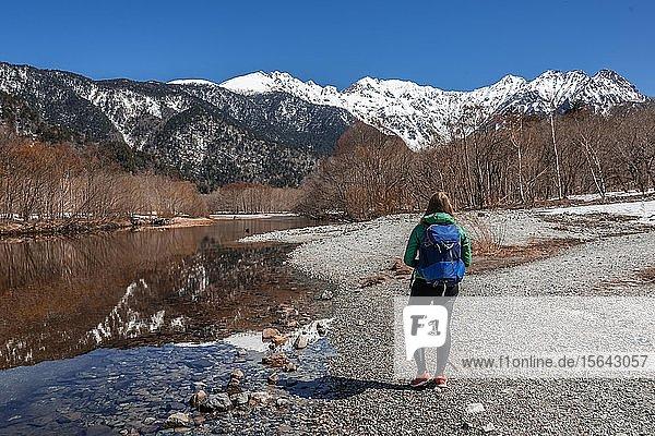 Junge Frau an einem See  Japanische Alpen spiegeln sich in Taisho Pond  hinten Mount Hotaka  Kamikochi  Matsumoto  Nagano