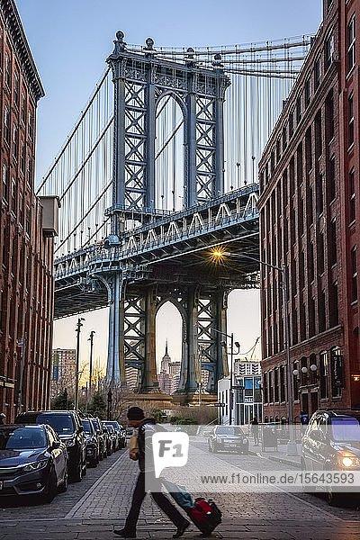 Tourist mit Rollkoffer überquert die Straße  Blick von Main Street auf Manhattan Bridge und Empire State Building  Morgenstimmung  Dumbo  Brooklyn  New York  USA  Nordamerika