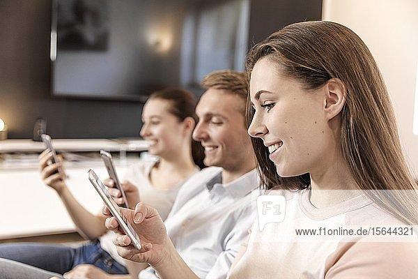 Freunde sitzen auf der Couch  lächeln  schauen auf ihr Smartphone  Deutschland  Europa