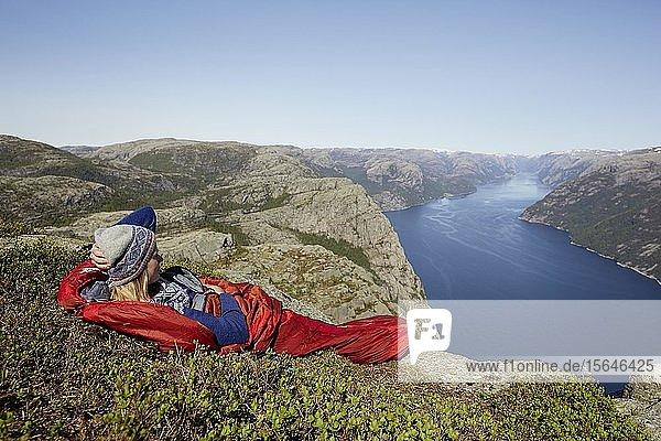 Junge Frau liegt im roten Schlafsack mit Blick über den Fjord  Outdoor  Camping  Preikestolen  Rogaland  Norwegen  Europa