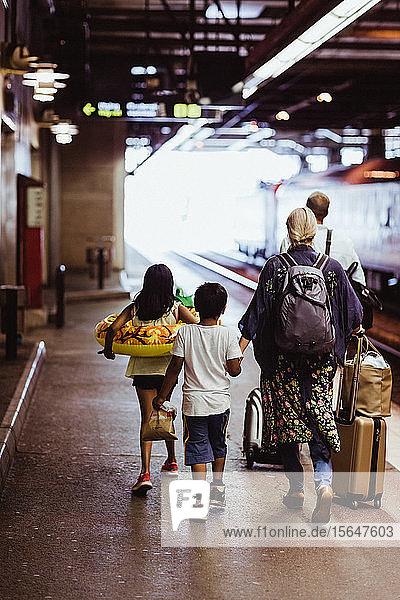 Familie in voller Länge mit Gepäck auf dem Bahnsteig am Bahnhof