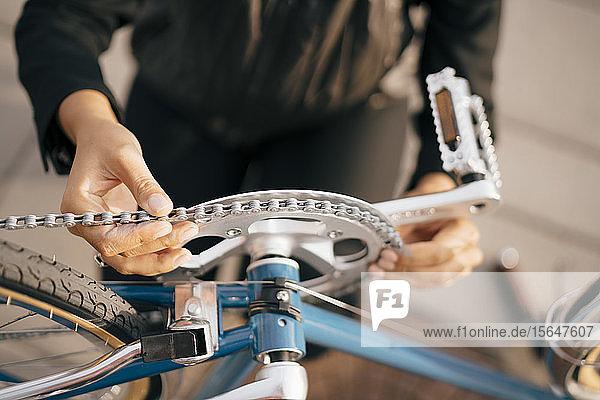Mittelteil einer Geschäftsfrau  die ein Fahrrad in der Stadt repariert