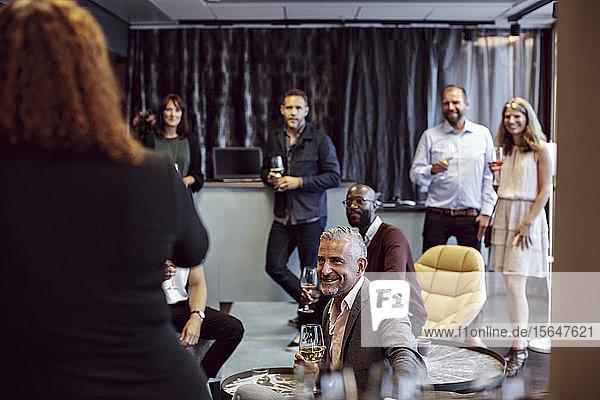 Männliche und weibliche Berufstätige hören einer Geschäftsfrau zu  die eine Rede auf einer Konferenz in einer Büropartei hält