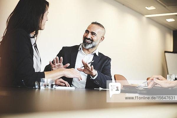 Männliche und weibliche Anwälte diskutieren am Konferenztisch im Sitzungssaal