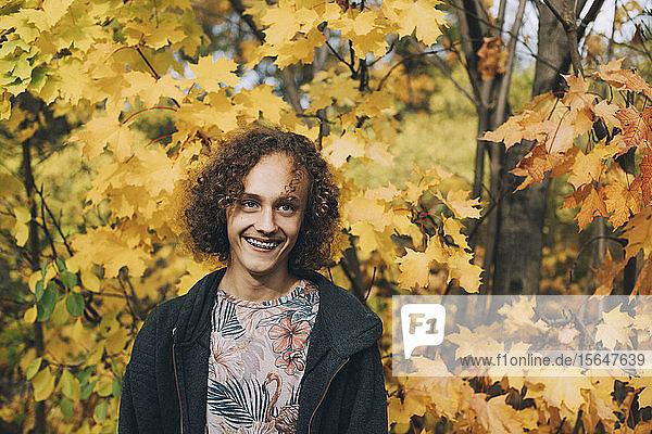 Fröhlicher Teenager mit Zahnspange und lockigem Haar  der im Herbst wegschaut