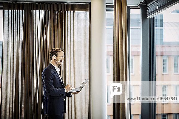 Lächelnder männlicher Jurist spricht durch blauen Zahn  während er seinen Laptop im Büro benutzt