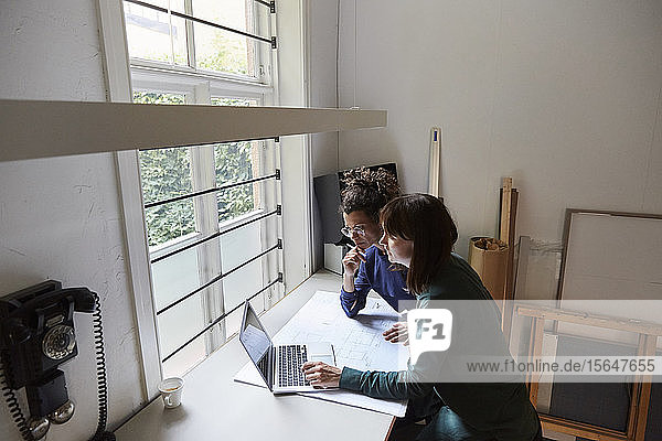 Female architects planning over laptop at table in office