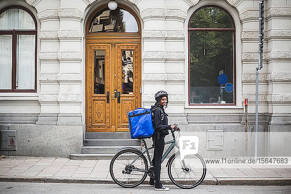 Side view portrait of smiling delivery woman with bicycle on street in city