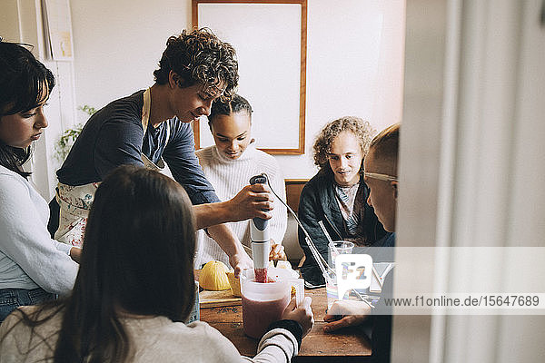 Friends looking at teenage boy preparing smoothie at dining table in room