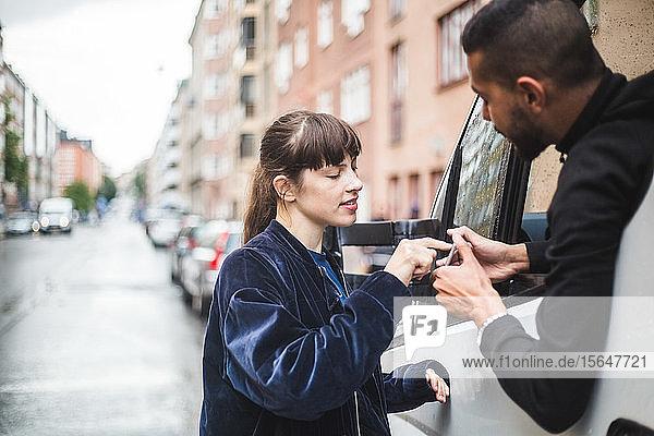 Weibliche Kunden  die auf einem Smartphone unterschreiben  werden von einem männlichen Spediteur im Lastwagen festgehalten