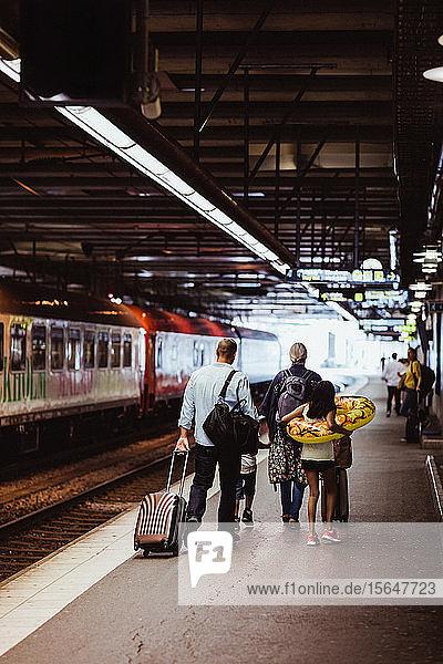 Eltern und Kinder gehen mit Gepäck auf dem Bahnsteig des Bahnhofs