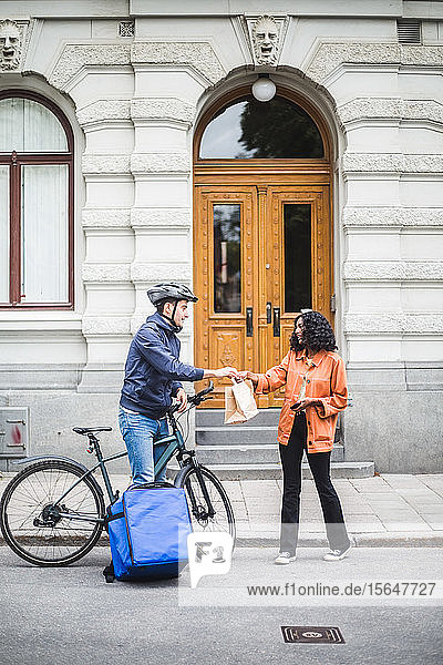 Food delivery man delivering package to woman standing on sidewalk in city