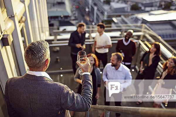 Ein reifer Geschäftsmann stoßt an  während er vor Kollegen auf der Terrasse eine Rede hält