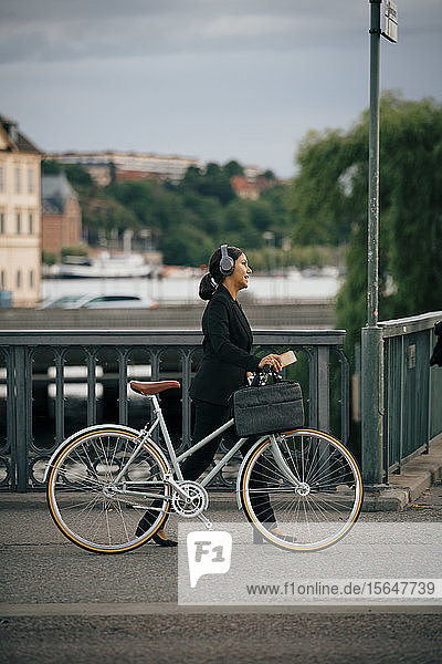 Side view of businesswoman walking with bicycle on bridge in city