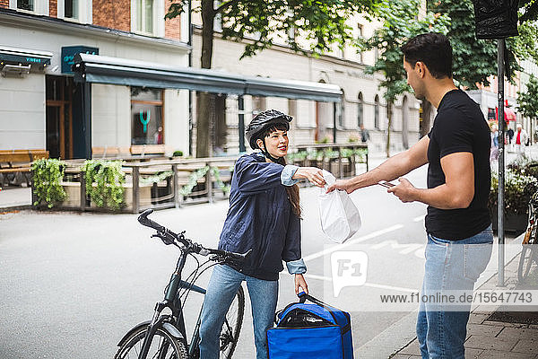 Food delivery woman giving package to male customer standing on sidewalk in city