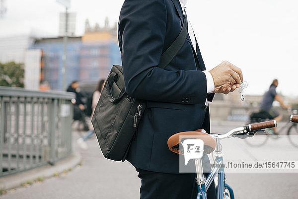 Geschäftsmann mit In-Ohr-Kopfhörern im Stehen mit Fahrrad auf einer Brücke in der Stadt