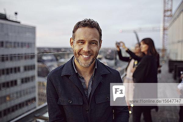 Porträt eines lächelnden Geschäftsmannes in eleganten Freizeitkleidern  der nach der Arbeit auf der Terrasse bei einer Büroparty feiert
