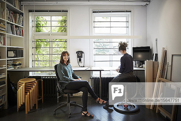 Portrait of female architect with coworker at table in office