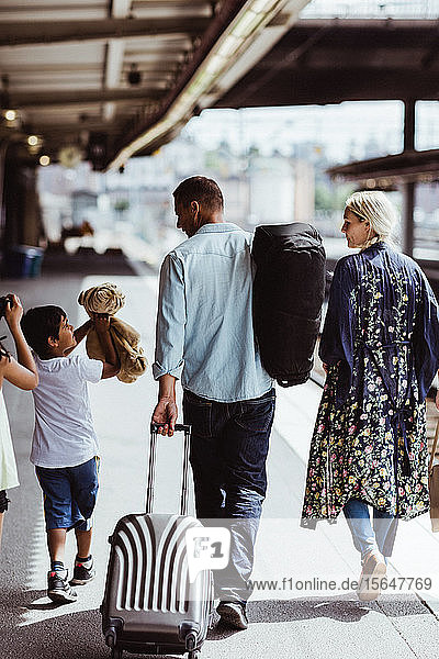 Rückansicht eines Mannes  der Gepäck hält  während er mit seiner Familie am Bahnhof spazieren geht