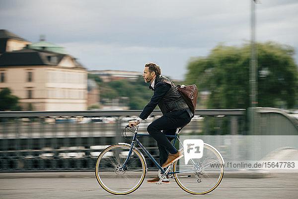 Full length of confident businessman riding bicycle on bridge