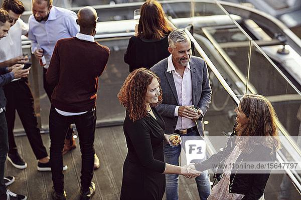 Schrägaufnahme einer Geschäftsfrau beim Händeschütteln und Begrüßen während einer Party mit Kollegen nach der Arbeit auf der Terrasse