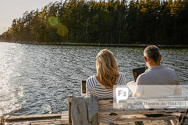 Rear view of couple using laptop while sitting on bench against lake