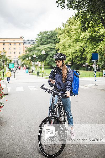 Essenslieferantin mit Mobiltelefon auf der Straße in der Stadt