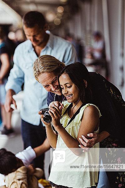 Glückliche Mutter und Tochter schauen in die Kamera  während sie bei der Familie am Bahnhof stehen