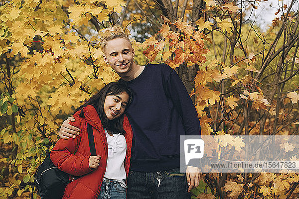 Lächelnde Teenager-Freunde stehen im Herbst an Ahornbäumen