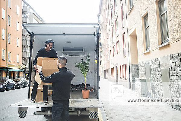 Männliche und weibliche Möbelpacker beim Entladen von Kisten vom Lastwagen auf der Straße in der Stadt