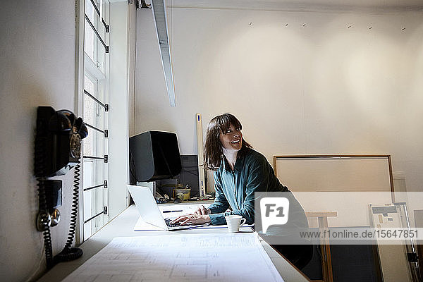 Smiling female architect looking away while using laptop in office