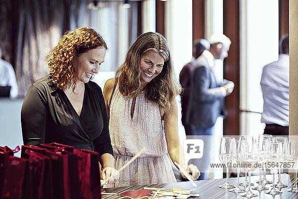 Lächelnde Geschäftsfrauen schauen auf Requisiten durch Weingläser auf dem Tisch in der Büroparty