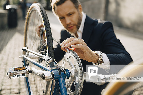 Businessman repairing bicycle chain in city on sunny day
