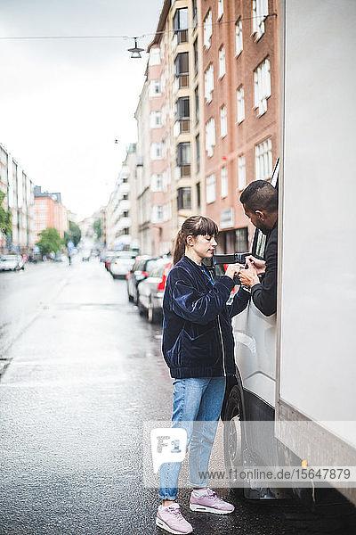 Junge Kunden  die auf einem Smartphone unterschreiben  werden von männlichem Spediteur im Lastwagen auf der Straße festgehalten